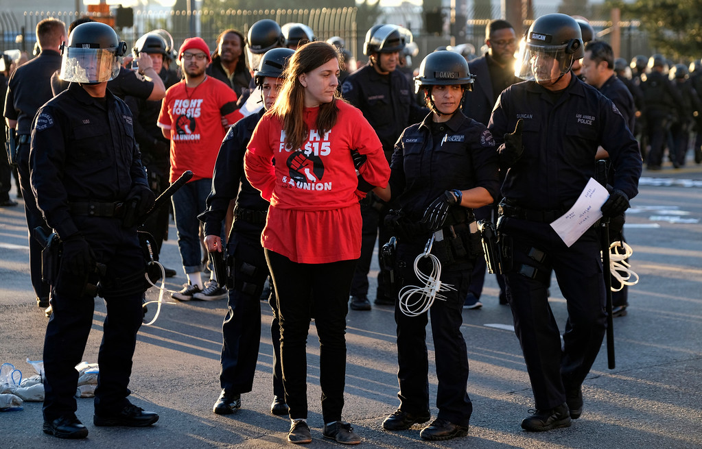 ". Protesters are arrested and taken into custody during a wage protest in downtown Los Angeles on Tuesday, Nov. 29, 2016. A few dozen protesters blocked a downtown Los Angeles intersection as part of a national wave of demonstrations in support of higher wages and workers\' rights. Police stood by as the peaceful demonstrators formed a circle in the street early Tuesday while hoisting signs saying ""the whole world is watching\"" and \""Fight for $15.\"" (AP Photo/Richard Vogel)"