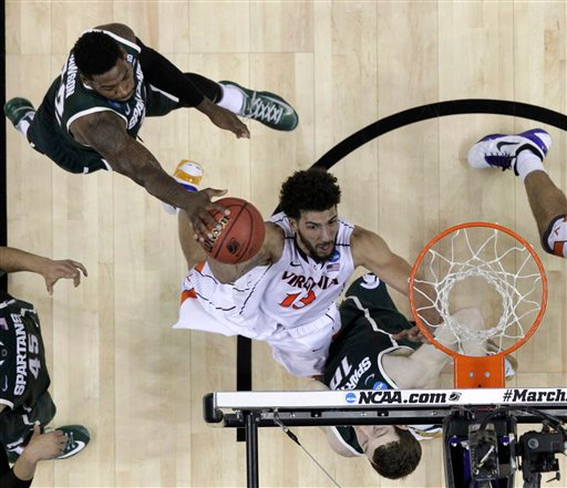. Virginia\'s Anthony Gill (13) drives to the basket against Michigan State during the first half of an NCAA tournament college basketball game in the Round of 32 in Charlotte, N.C., Sunday, March 22, 2015. Michigan State won 60-54. (AP Photo/Gerald Herbert)