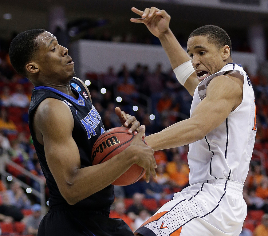 . Virginia guard Malcolm Brogdon (15) collides with Memphis Nick King (5) during the second half of an NCAA college basketball third-round tournament game, Sunday, March 23, 2014, in Raleigh, N.C. (AP Photo/Chuck Burton)