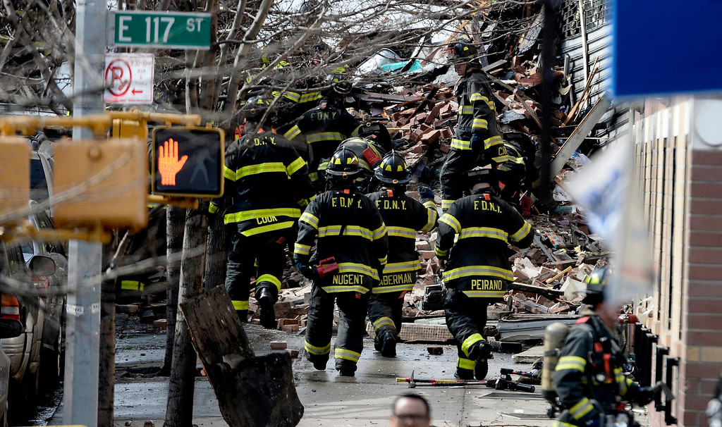 . Firefighters on the scene where a group of buildings were damaged by fire and a possible explosion in New York, New York, USA, 12 March 2014.  EPA/ANDREW GOMBERT