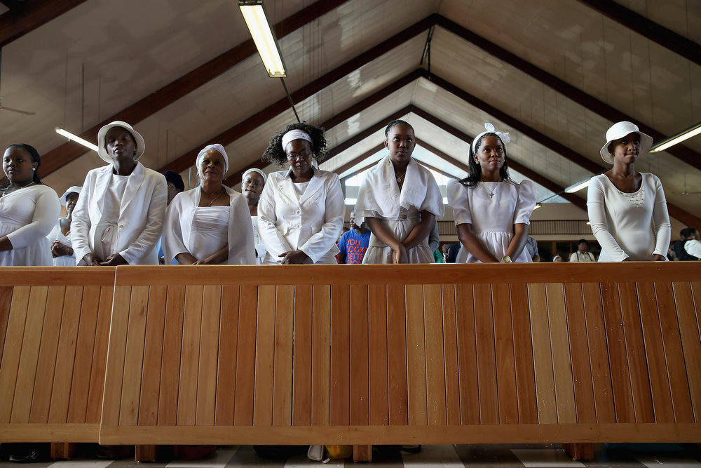 """. Congregants pray during Easter services at Regina Mundi Catholic Church in the Soweto area March 31, 2013 in Johannesburg, South Africa. A central gathering place during he anti-apartheid struggle, the church held prayers for former South African President Nelson Mandela, 94, who is in the hospital for the third time since December with lung problems. Referring to Mandela by clan name, Madiba, President Jacob Zuma said, \""""We appeal to the people of South Africa and the world to pray for our beloved Madiba and his family and to keep them in their thoughts.\"""" Mandela\'s lungs were damaged when he contracted tuberculosis during his 27 years in the infamous Robben Island prison. Mandela became the nation\'s first democratically elected president in 1994 following the end of apartheid.  (Photo by Chip Somodevilla/Getty Images)"""