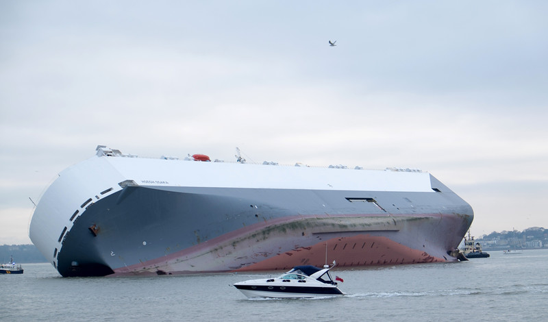 . A small boat sails past the Hoegh Osaka car transporter cargo ship that ran aground in the Solent, off the Isle of Wight Sunday Jan. 4, 2015. The crew members of the Hoegh Osaka were taken to safety by a coastguard helicopter and lifeboats after it became stranded on Bramble Bank, in the Solent between Southampton and the Isle of Wight. (AP Photo/ Francis Bigg Photography)
