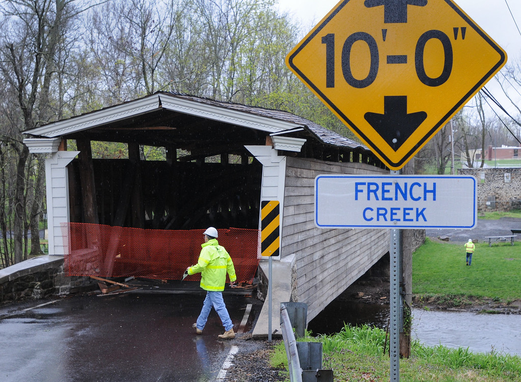 . Officials inspect the Rapps Dam Bridge in East Pikeland Township Tuesday afternoon after the operator of a tractor trailer drove his truck through the covered bridge causing structural damage to beams and the roof. The sign at right shows the height of the bridge at 10 feet. Photo by John Strickler The Mercury