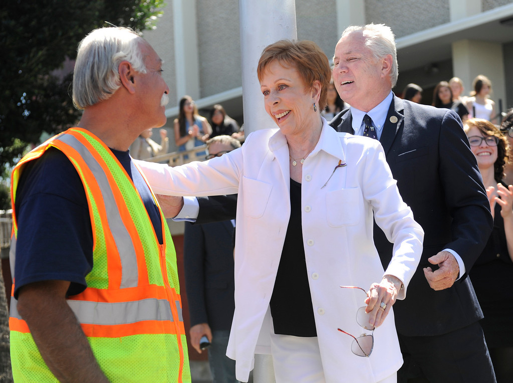 """. Carol Burnett gives a hug to the sign painter. Burnett, award-winning actress, comedienne and best-selling author, was honored by the City of Los Angeles for her lifetime achievements with the naming of Carol Burnett Square at the intersection of Highland Avenue and Selma Avenue. The Square is adjacent to Hollywood High School where Burnett attended. Students from the school choir, \""""H2O\"""" sang �I�m so glad we had this time together,� before Burnett and LA City Councilman Tom LaBonge unveiled her street sign. Hollywood, CA 4/18/2013(John McCoy/Staff Photographer"""