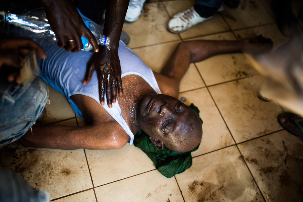 . Protestors  pour  water on a  injured man near the parliament building in Burkina Faso as people protest  against their longtime president Blaise Compaore who is  seeking another term in Ouagadougou, Burkina Faso, Thursday, Oct. 30, 2014. (AP Photo/Theo Renaut)