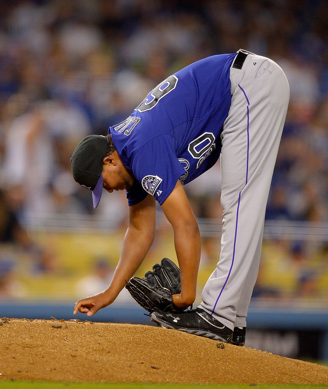 . Colorado Rockies relief pitcher Manny Corpas writes something in the mound during the sixth inning of their baseball game against the Los Angeles Dodgers, Thursday, July 11, 2013 in Los Angeles.  (AP Photo/Mark J. Terrill)