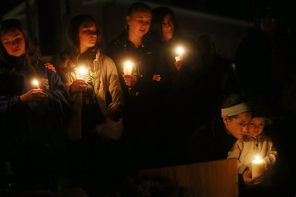 . NEWTOWN, CT - DECEMBER 16: (L-R) Newtown residents Claire Swanson, Kate Suba, Jaden Albrecht, Simran Chand and New London, Connecticut residents Rachel Pullen and her son Landon DeCecco, hold candles at a memorial for victims on the first Sunday following the mass shooting at Sandy Hook Elementary School on December 16, 2012 in Newtown, Connecticut. U.S. President Barack Obama visited the grief stricken town today. (Photo by Mario Tama/Getty Images)
