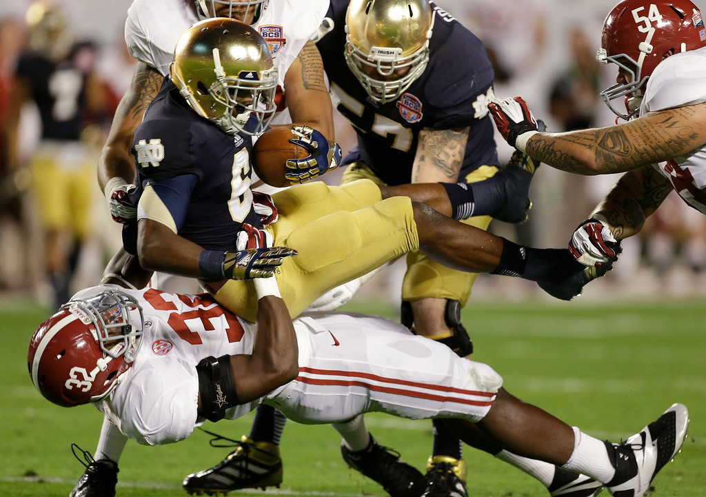 . Alabama\'s C.J. Mosley (32) takes down Notre Dame\'s Theo Riddick (6) during the first half of the BCS National Championship college football game Monday, Jan. 7, 2013, in Miami. (AP Photo/Chris O\'Meara)