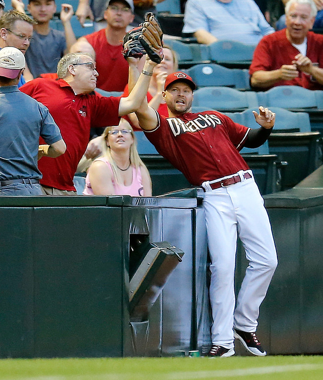 . Arizona Diamondbacks\' Cody Ross  catches a foul ball hit by Colorado Rockies\' Troy Tulowitzki around a fan  during the first inning of a baseball game on Wednesday, April 30, 2014, in Phoenix. (AP Photo/Matt York)