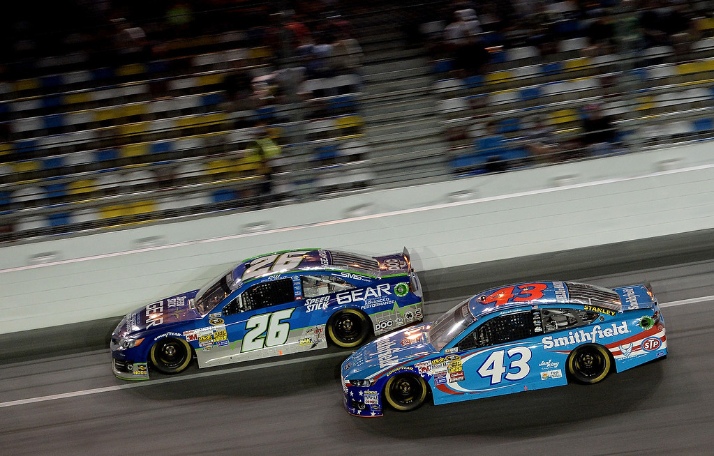 . Cole Whitt, driver of the #26 Speed Stick Gear Toyota, and Aric Almirola, driver of the #43 Smithfield Ford, race during the NASCAR Sprint Cup Series Budweiser Duel 1 at Daytona International Speedway on February 20, 2014 in Daytona Beach, Florida.  (Photo by Patrick Smith/Getty Images)