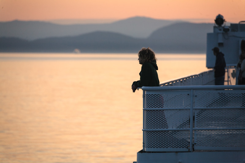 A woman looks out over the water is after sunset on a British Columbia ferry - , Capital, British Columbia, Canada (CA)