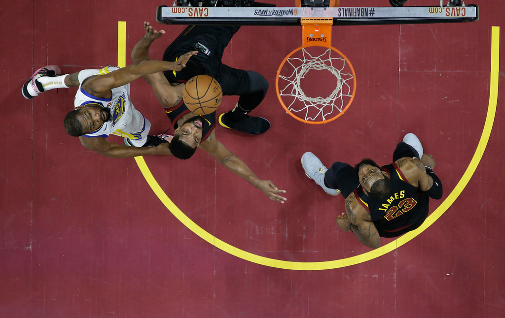 . Golden State Warriors\' Kevin Durant and Cleveland Cavaliers\' Tristan Thompson battles for a rebound as LeBron James, right, watches in the first half of Game 3 of basketball\'s NBA Finals, Wednesday, June 6, 2018, in Cleveland. (AP Photo/Carlos Osorio, Pool)