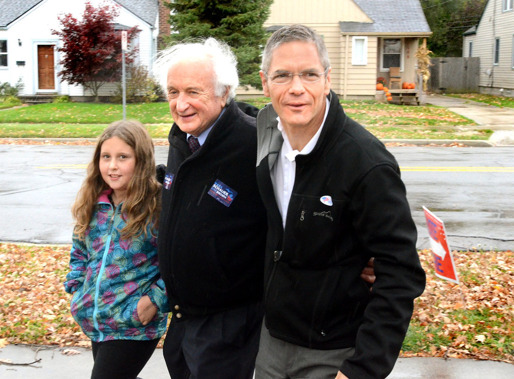 . Democratic gubernatorial candidate Mark Schauer, right, along with congressman Sandy Levin and Levin\'s granddaughter Molly Levin, 9, visit the polling place at the Salter Community Center in Royal Oak.    Tuesday, November 4, 2014.  Tim Thompson-The Oakland Press