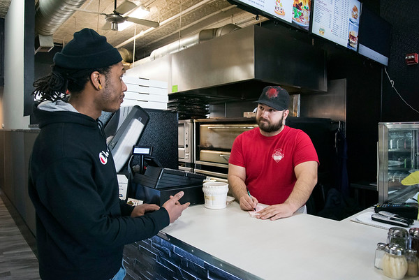 03/27/20 Wesley Bunnell | StaffrrDale Marshall, L, owner of City Ink Tattoo places a take out order with Bes Ramadani at Peppinos Pizza at 10 Main St on Monday afternoon. Governor Ned Lamont ordered all restaurants closed effective at 8 p.m. with the exception of take out and delivery.
