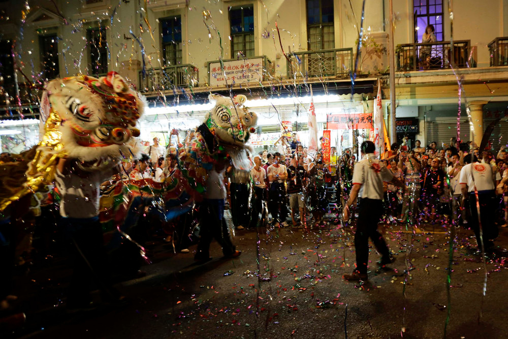 Description of . Confetti falls as lion dance troupes perform on a street during a ceremony to celebrate the Lantern Festival in Singapore's Chinatown district February 24, 2013. The festival which is also known as Yuan Xiao Jie is a Chinese festival celebrated on the 15th day of the first month of the lunar year. It also marks the end of the series of celebrations starting from the Chinese New Year. REUTERS/Tim Chong