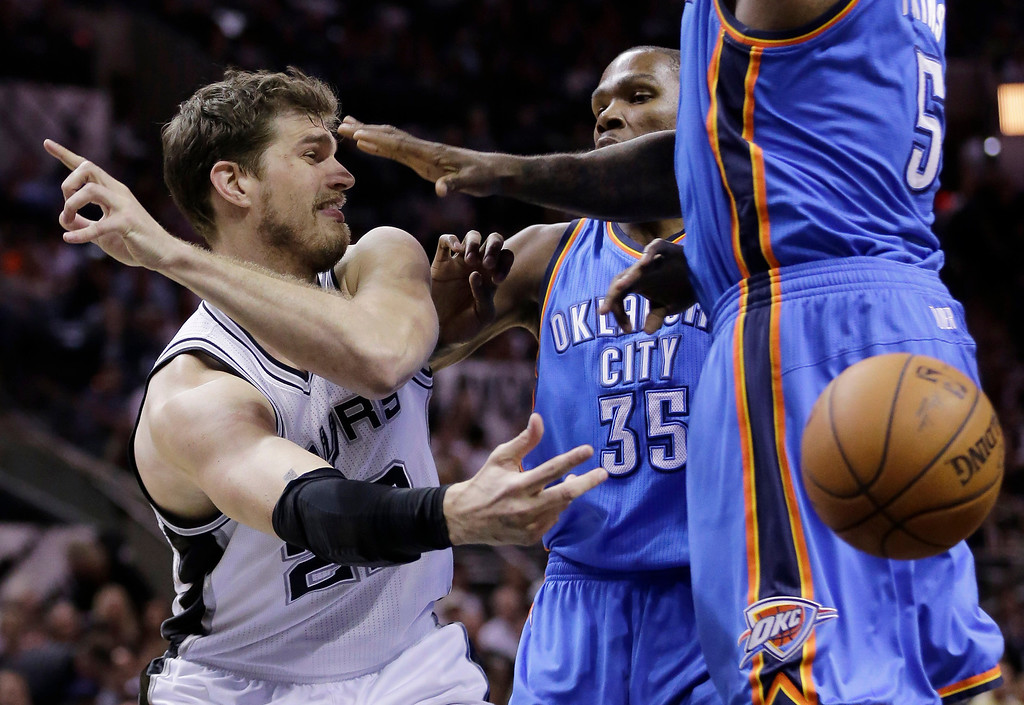 . San Antonio Spurs\' Tiago Splitter (22), of Brazil, passes the ball around Oklahoma City Thunder\'s Kevin Durant (35) and Kendrick Perkins (5) during the first half of Game 2 of the Western Conference finals in the NBA basketball playoffs, Wednesday, May 21, 2014, in San Antonio. (AP Photo/Eric Gay)