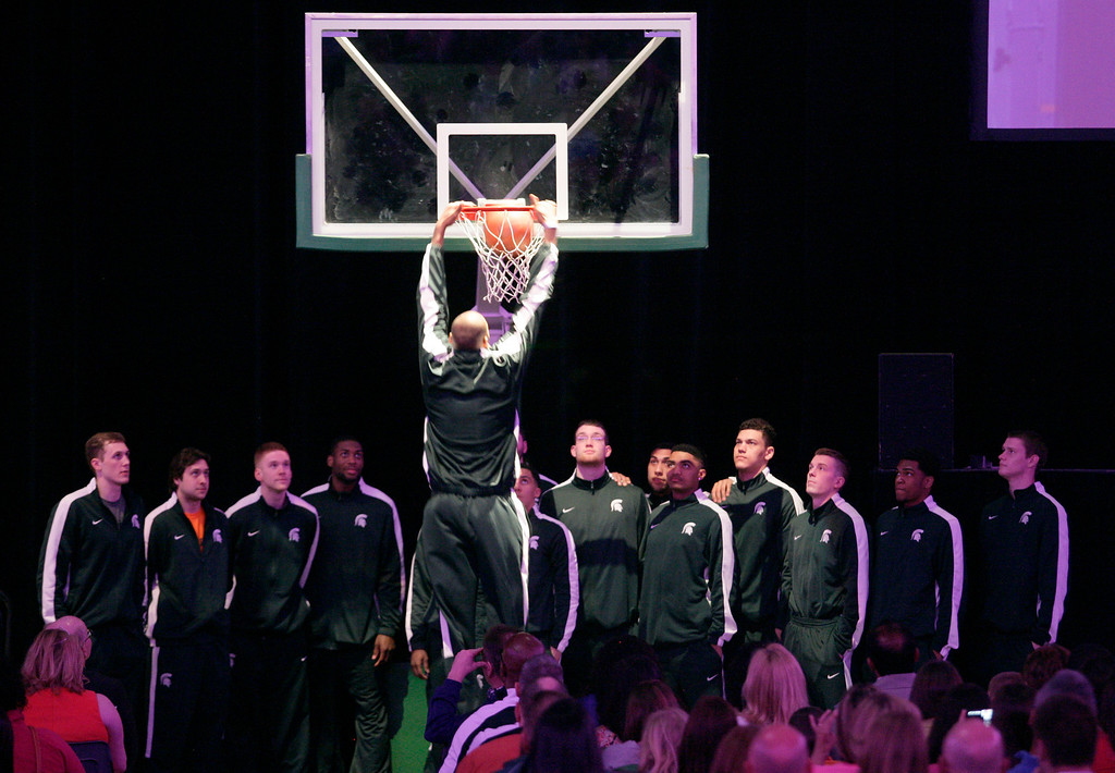 """. Michigan State basketball player Adreian Payne performs a \""""moment of silence dunk\"""" during a memorial to celebrate the life and legacy of Lacey Holsworth, an 8-year-old Michigan State basketball fan whose battle with cancer inspired the team\'s players, coaches and many more beyond the hardwood on Thursday, April 17, 2014, at Michigan State University\'s Breslin Center in East Lansing, Mich. (AP Photo/Al Goldis)"""