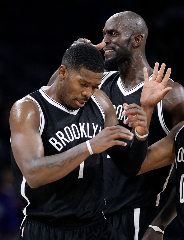 . Brookyn Nets\' Joe Johnson, left, receives a pat on the head from teammate Kevin Garnett after sinking a three-point basket during the fourth quarter of an NBA basketball game against the Detroit Pistons Saturday, Nov. 1, 2014, in Auburn Hills, Mich. Johnson led the Nets with 34 points in a 102-90 win.(AP Photo/Duane Burleson)