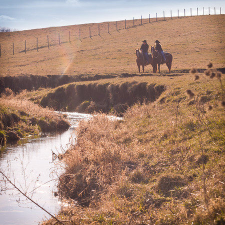 Couple horseback riding near creek at Perks Ranch during winter engagement photos in Rockford, IL