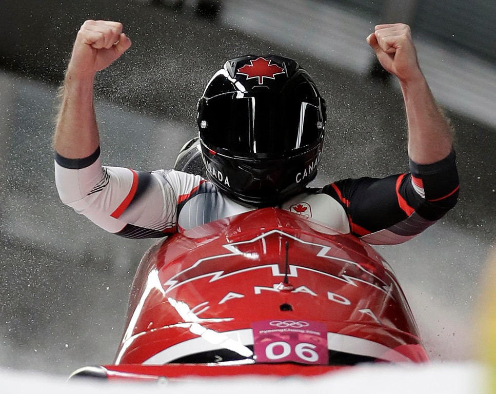 . Driver Justin Kripps and Alexander Kopacz of Canada celebrate as they cross the finish area after tying for the gold with Germany during the two-man bobsled final at the 2018 Winter Olympics in Pyeongchang, South Korea, Monday, Feb. 19, 2018. (AP Photo/Michael Sohn)