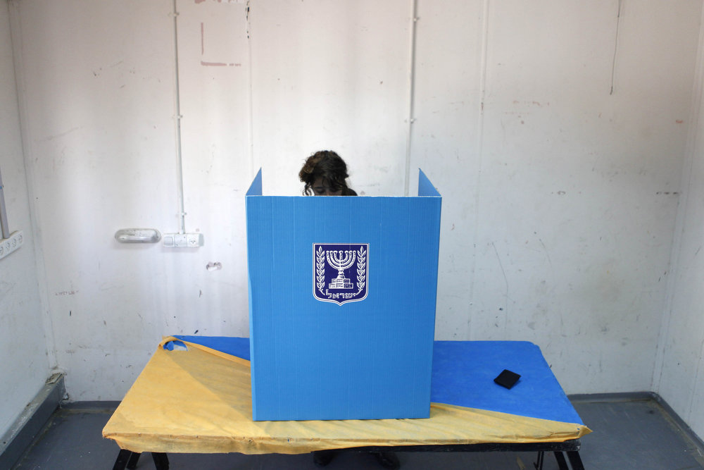 Description of . An Israeli soldier casts her vote at an army base on January 21, 2013 in Shekef, Israel. The Israeli general election will be held on January 22.  (Photo by Lior Mizrahi/Getty Images)