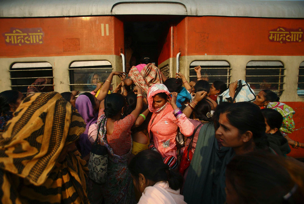 Description of . Women try to enter the ladies' compartment of a crowded train heading towards Delhi at Noli Railway Station in Utter Pradesh November 10, 2012. In India some train compartments, or sometimes whole trains, are reserved specifically for female passengers in an effort to make their travel easier and more secure. The role and treatment of women in society has recently become a hot political issue in the country, since the Dec. 16 gang rape of a 23-year-old student in New Delhi, who later died of her injuries, and whose case has led to widespread protests in the region against violence against women. Picture taken November 10, 2012. REUTERS/Navesh Chitrakar