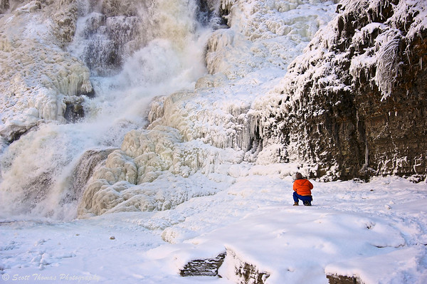 A lone photographer in front of ice encased Ithaca Falls in Ithaca, New York during the winter.
