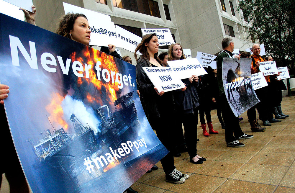 . Activists holds signs during a protest in front of the Hale Boggs Federal Building on the first day of the trial over the Deep Water Horizon oil rig spill on February 25, 2013 in New Orleans, Louisiana. 11 men were killed during the accident and over 4 million barrels of oil spilled into the Gulf of Mexico in 2010. (Photo by Sean Gardner/Getty Images)