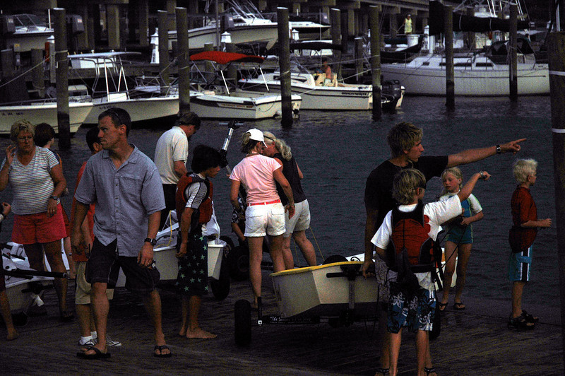 Parents and coaches help retrieve boats as inclimate weather approaches.