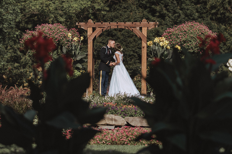 The bride and groom kiss under a garden arbor surrounded by flowers.