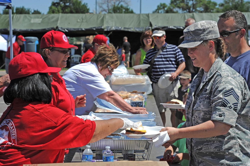 . Colorado National Guard member Holly Allen gets lunch served to her by Brenda Bell Ennis, left and other volunteer members of the Emergency Disaster Services of the Salvation Army at Buckley Air Force base in Aurora, CO on August 4, 2013.  The event was part of the 140th Wing Family Day for members of the Colorado National Guard.  Much of the money raised during the day goes to the Colorado National Guard Family Support System that helps take care of families when their loved ones have been deployed.  The Salvation Army was on hand to show their continued support for the armed services.  Photo by Helen H. Richardson/The Denver Post)