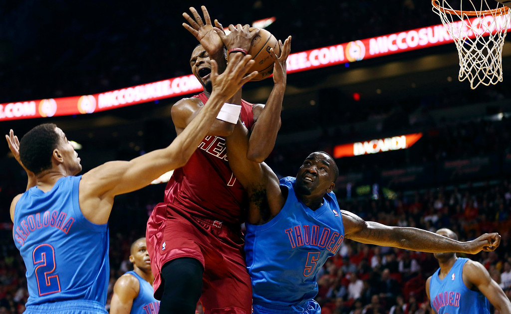 . Oklahoma City Thunder\'S Thabo Sefolosha (2) and Kendrick Perkins (5) defend Miami Heat\'s Chris Bosh (1) during the first half of an NBA basketball game, Tuesday, Dec. 25, 2012, in Miami. (AP Photo/J Pat Carter)