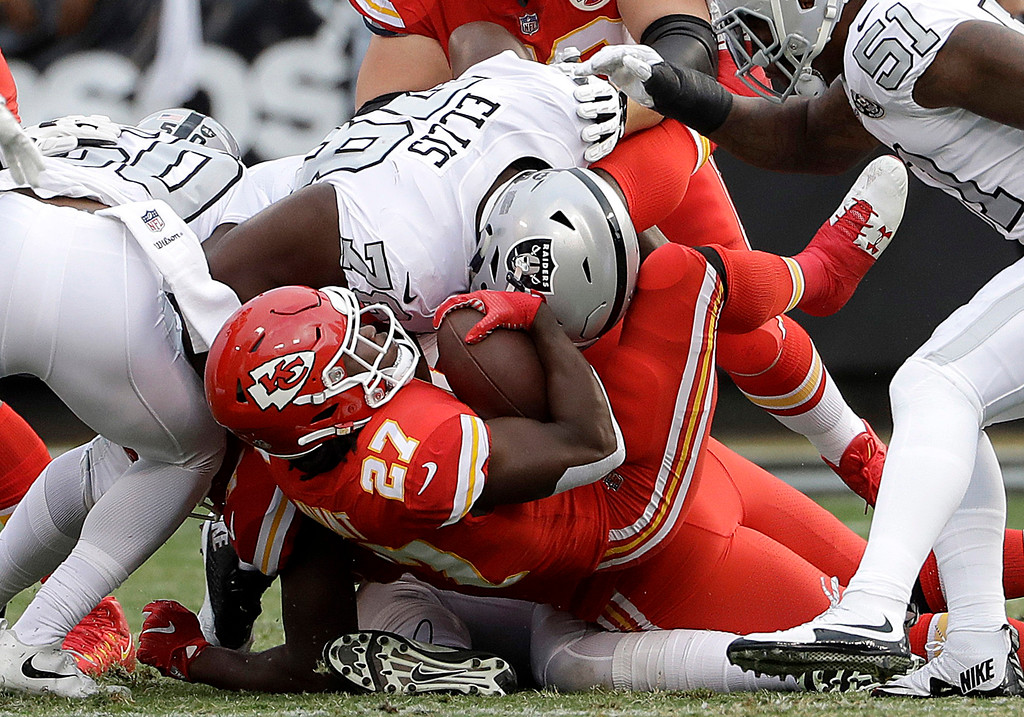 . Kansas City Chiefs running back Kareem Hunt (27) is tackled by Oakland Raiders defensive tackle Justin Ellis (78) and linebacker Nicholas Morrow (50) during the first half of an NFL football game in Oakland, Calif., Thursday, Oct. 19, 2017. (AP Photo/Marcio Jose Sanchez)