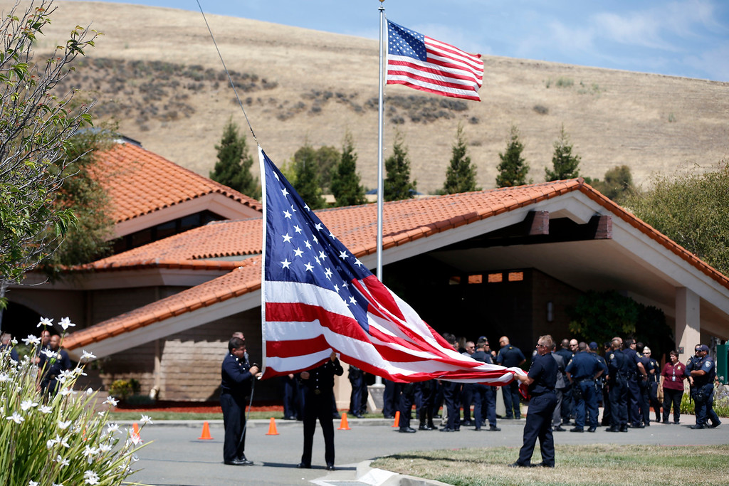 . Hayward firefighters bring down an American flag at the conclusion of the procession with the body of Hayward police Sgt. Scott Lunger from the Coroner\'s Bureau in Oakland to Chapel of the Chimes Memorial Park in Hayward, Calif., on Thursday, July 23, 2015. Lunger was killed during a traffic stop in early Wednesday. (Ray Chavez/Bay Area News Group)