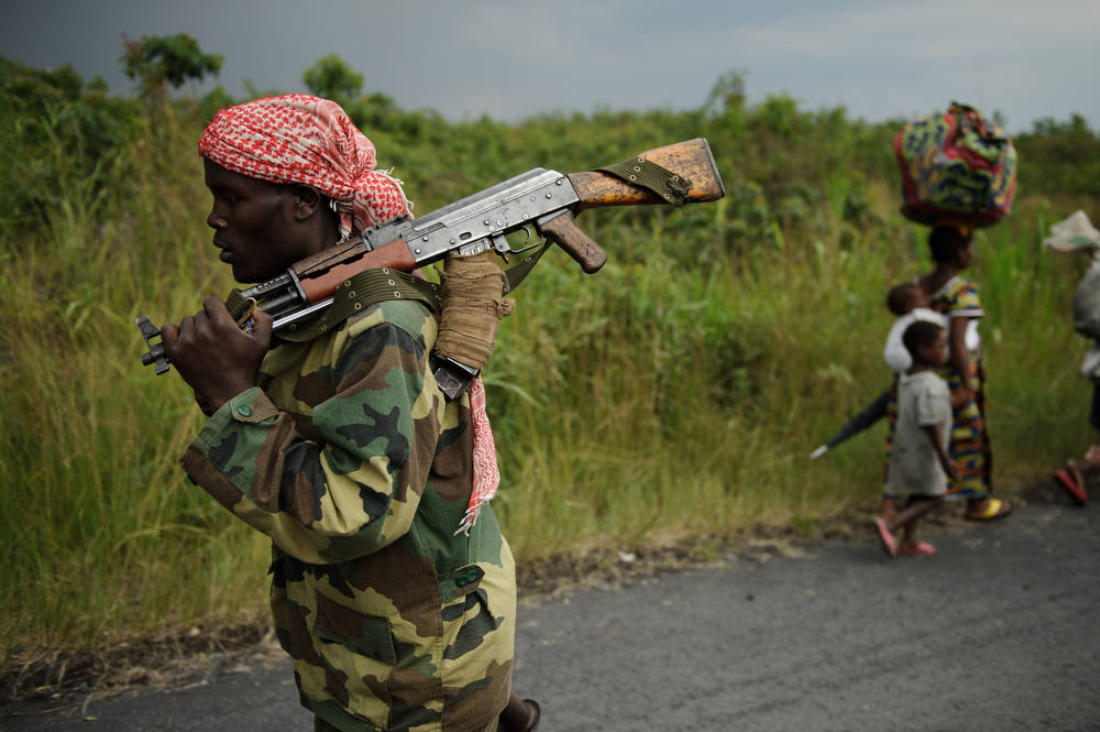 Description of . An M23 rebel marches towards the town of Sake, 26km west of Goma, as thousands of residents flee fresh fighting in the eastern Democratic Republic of the Congo town on November 22, 2012. Fighting broke out this afternoon causing people to flee the town and head east, towards Goma, to the camps for the internally displaced in the village of Mugunga. AFP PHOTO/PHIL MOORE/AFP/Getty Images
