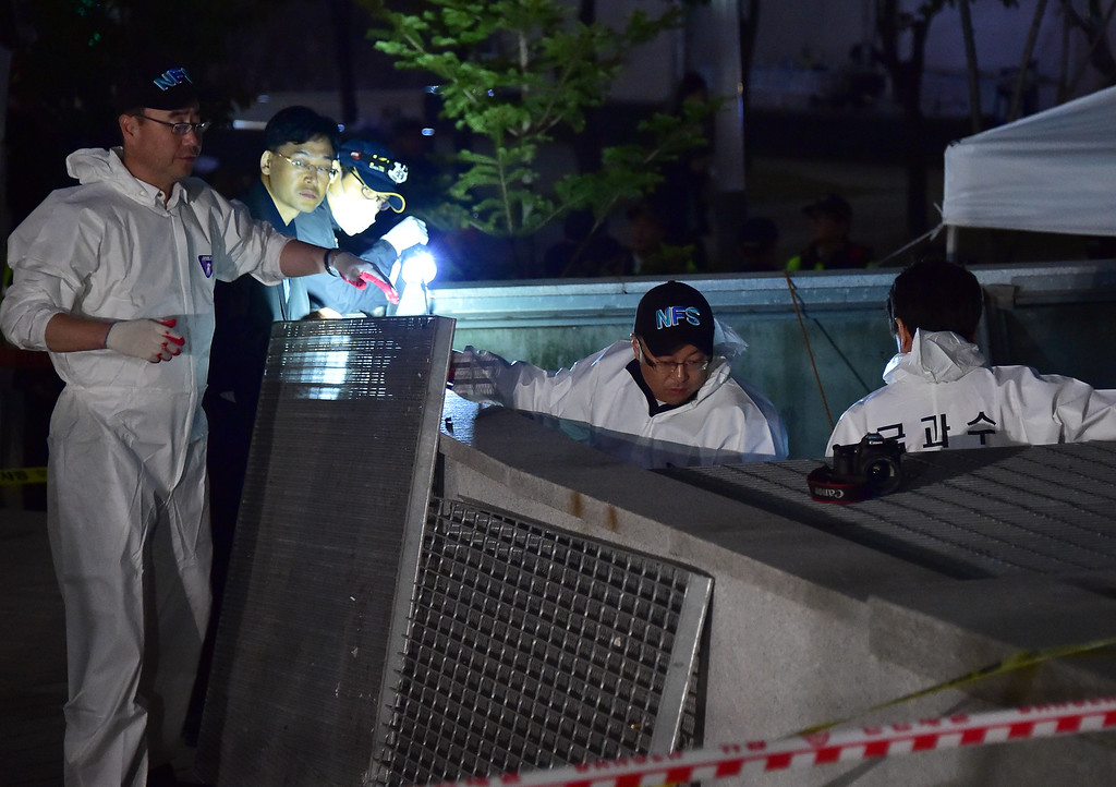 . South Korean National Forensic Service members check a broken ventilation grate after concert goers fell through it into an underground parking area below in Seongnam City, south of Seoul, on October 17, 2014.   AFP PHOTO / JUNG YEON-JE/AFP/Getty Images