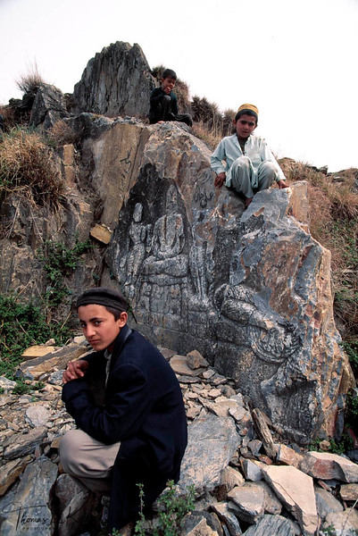 Another area popular with the men to look for fair complexioned boys is at some of the Buddhist historic sites. The under ground meditation rooms originally used by the monks now suite other purposes. Afgan boy sits on the ruined stone image of Padmasambava, Guru Rimpoche in Swat Valley.