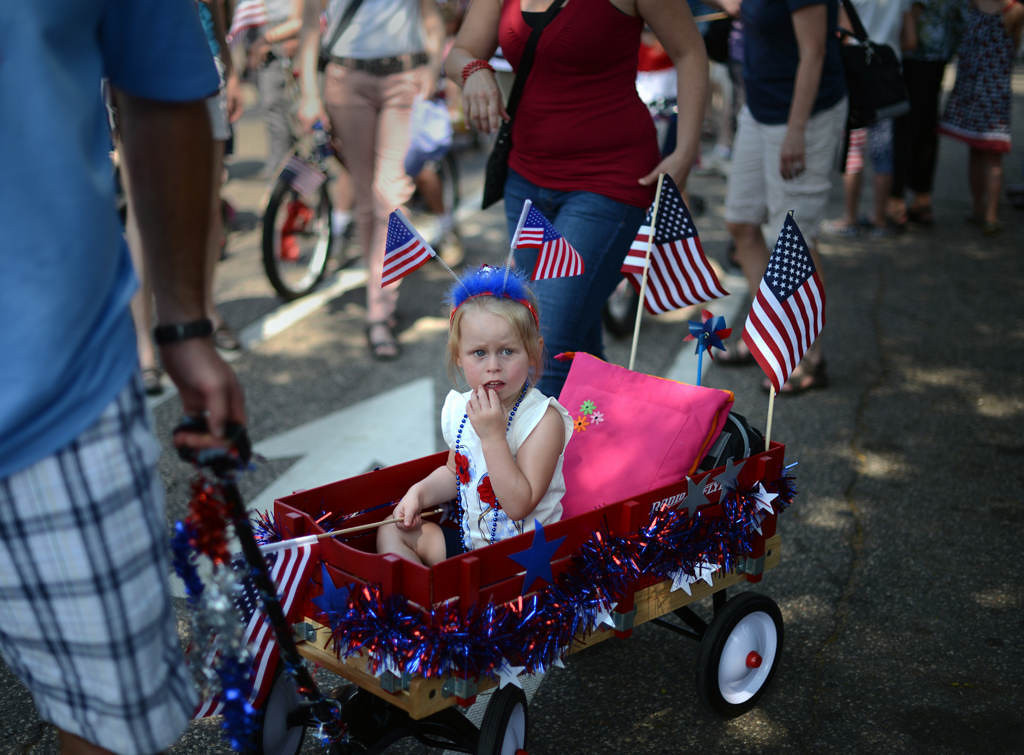 . A girl is pulled along in a wagon as children and families joined in at the rear of the Fourth in the Park parade and celebration, on their way to Langford Park where the Fourth of July festivities continued throughout the day.(Pioneer Press: Chris Polydoroff)