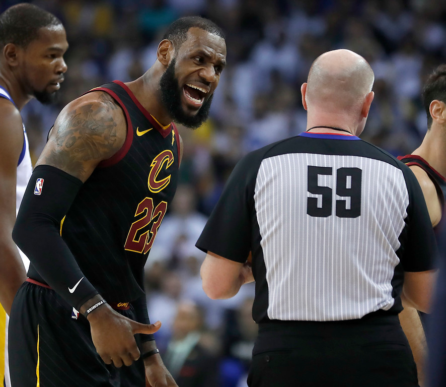 . Cleveland Cavaliers forward LeBron James (23)argues a call with referee Gary Zielinski (59) during the first half against the Golden State Warriors of an NBA basketball game in Oakland, Calif., Monday, Dec. 25, 2017. (AP Photo/Tony Avelar)