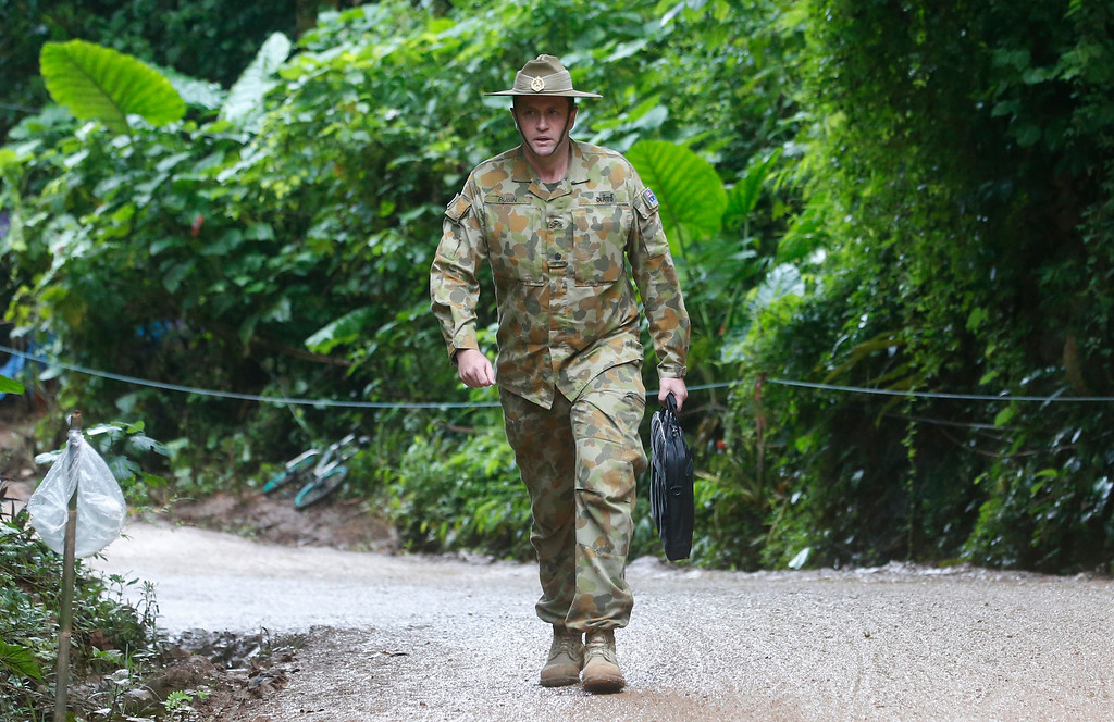 . Australian Federal Police and Defense Force personnel arrive near a cave where 12 boys and their soccer coach have been trapped since June 23, in Mae Sai, Chiang Rai province, in northern Thailand Sunday, July 8, 2018. Thai authorities are racing to pump out water from the flooded cave before more rains are forecast to hit the northern region. (AP Photo/Sakchai Lalit)