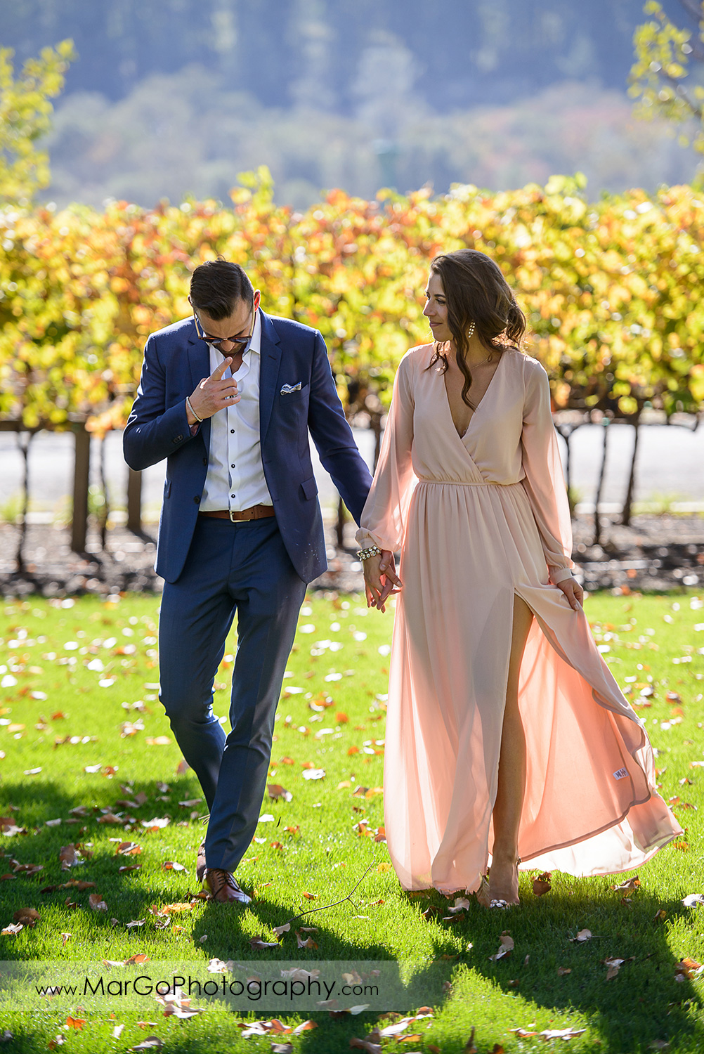 man in blue suit and woman in pink dress holding hands and walking during Napa Valley engagement session at Castello di Amorosa in Calistoga
