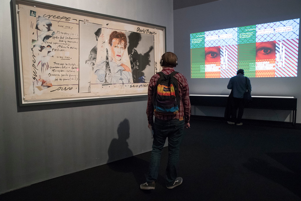 """. A visitor inspects Edward Bell\'s \""""Scary Monsters (and Super Creeps)\"""", during the media preview of the \""""David Bowie is\"""" exhibit at the Brooklyn Museum, Wednesday, Feb. 28, 2018, in New York. The exhibit opens to the public on March 2 and runs through July 15. (AP Photo/Mary Altaffer)"""