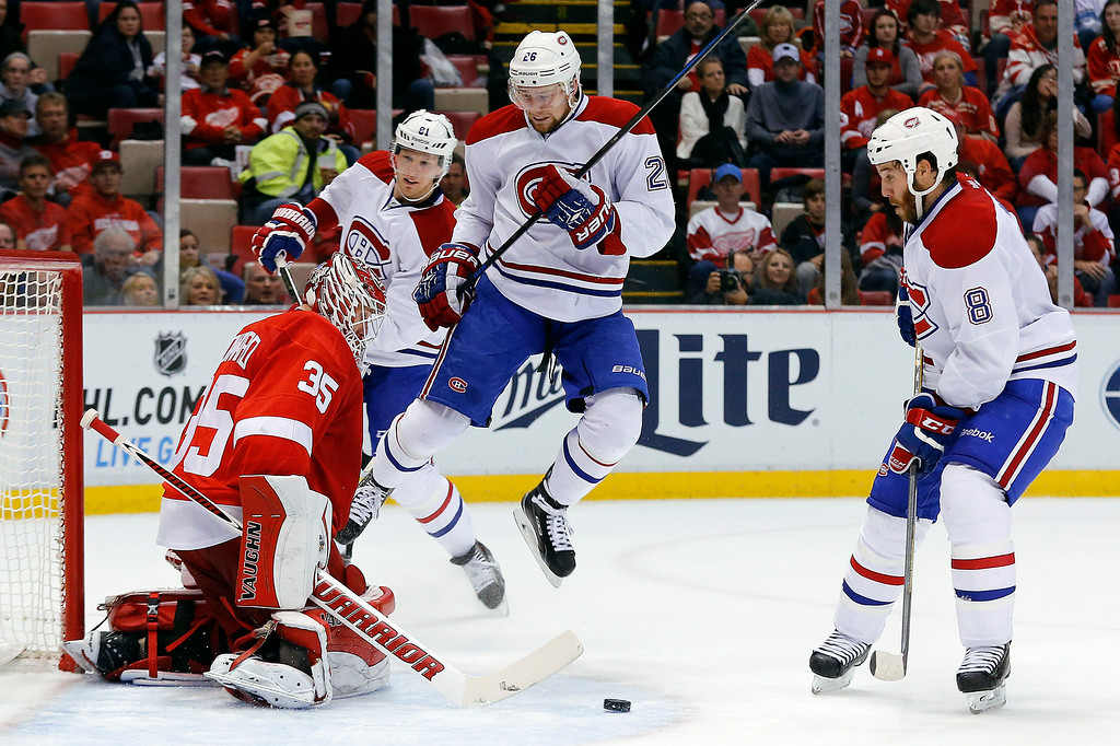 . Montreal Canadiens left wing Jiri Sekac (26) jumps to make room for a Brandon Prust (8) shot as Detroit Red Wings goalie Jimmy Howard (35) defends in the second period of an NHL hockey game in Detroit Sunday, Nov. 16, 2014. (AP Photo/Paul Sancya)