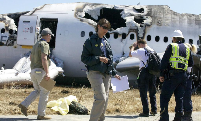 . National Transportation Safety Board investigators work Sunday, July 7, 2013, on their investigation into the cause of Saturday\'s crash of Asiana Flight 214, a Boeing 777 aircraft, at San Francisco International Airport. Two people were killed and close to 200 injured in the crash. (NTSB)
