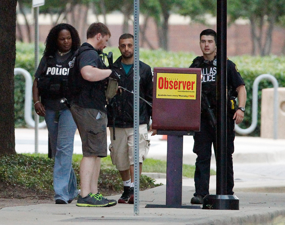 . Dallas police officers check a newspaper dispenser as they walk down Belleview Street one block away from police headquarters searching the area Saturday, June 13, 2015, in Dallas.  Police Chief David Brown says a police sniper has shot the suspect in an overnight attack on police headquarters and that the department is checking to see if he\'s still alive. Brown says investigators believe the man acted alone in the early-morning attack on Dallas police headquarters, despite early witness reports that others may have taken part.   (AP Photo/Tony Gutierrez)