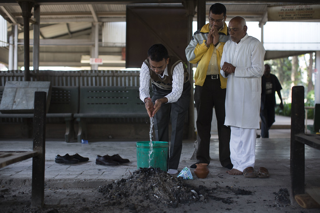 . Umesh Mashru pours water over the ashes of his neice Neha Mashru who was killed at the at the Westgate Mall attack, a day after her funeral ceremony on September 26, 2013 in Nairobi, Kenya. The country is observing three days of national mourning as security forces begin the task of clearing and securing the Westgate shopping mall following a four-day siege by militants. (Photo by Uriel Sinai/Getty Images)