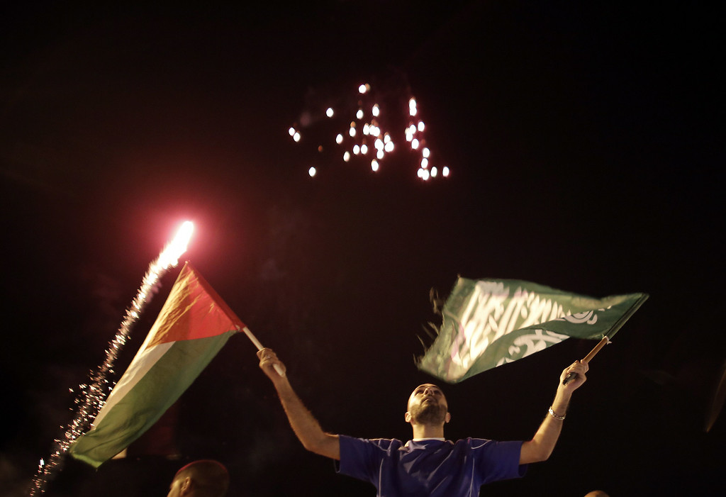 """. A Palestinian waves a national and a Hamas flag as fireworks light up the sky on August 26, 2014 in East Jerusalem as Palestinians celebrate in the streets the long-term truce agreed between Israel and the Palestinians. Israel has agreed to observe an \""""unlimited\"""" ceasefire in the Gaza Strip, a senior official told AFP, shortly after the deal was announced by the Palestinians AHMAD GHARABLI/AFP/Getty Images"""