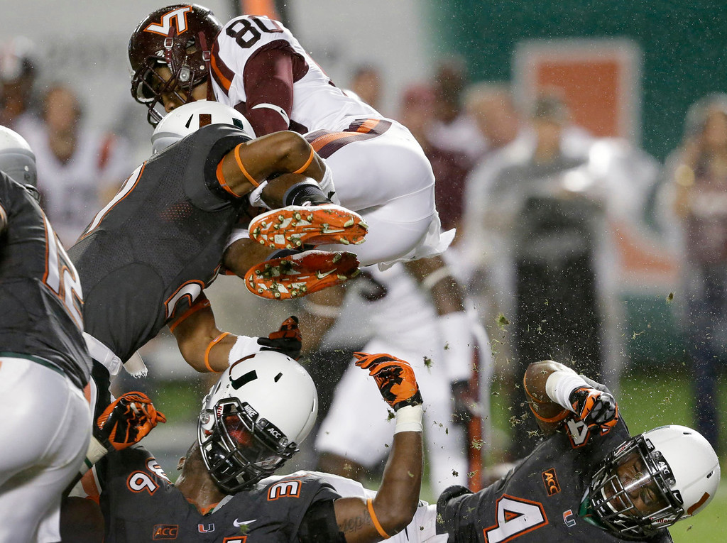 . Virginia Tech wide receiver Demitri Knowles (80) leaps over Miami defenders during the first half of an NCAA college football game, Saturday, Nov. 9, 2013, in Miami Gardens, Fla. (AP Photo/Wilfredo Lee)
