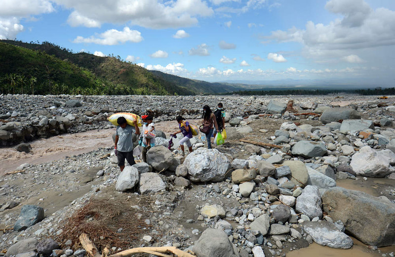 . A family carrying food relief for victims of Typhoon Bopha walks along a river as they head for home in the village of Andap in the town of New Bataan in the Compostela Valley province on December 8, 2012.  Hungry and homeless typhoon survivors appealed for help on December 8 as the ravaged southern Philippines mourned its more than 500 dead and desperate people in one hard-hit town looted shops in search of food.      AFP PHOTO / TED  ALJIBE/AFP/Getty Images