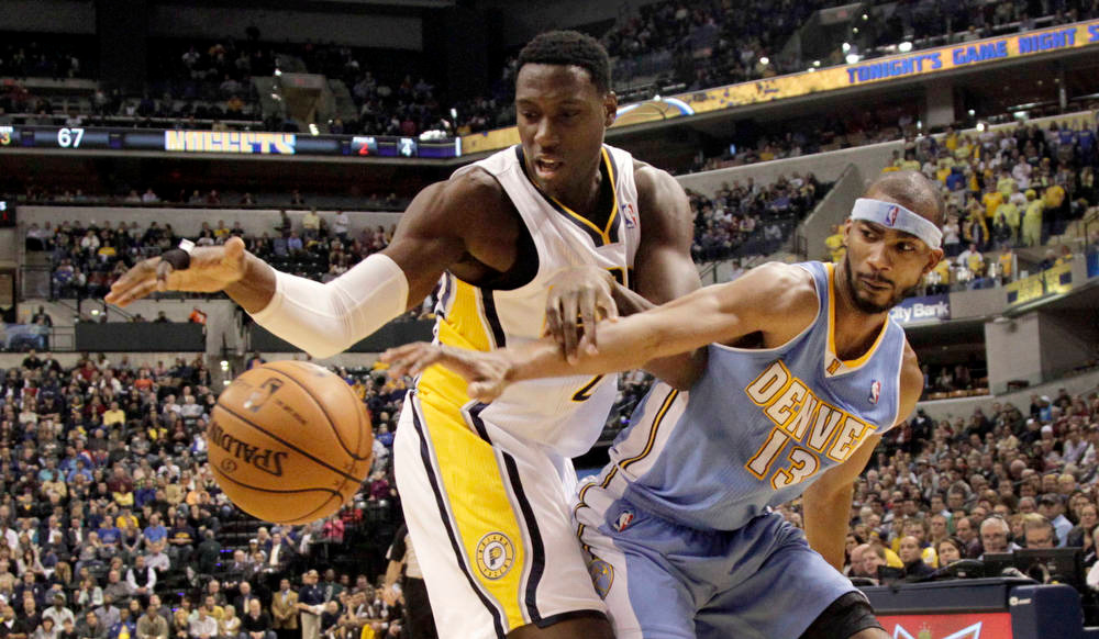 . Indiana Pacers center Ian Mahinmi,left, of France, struggles for control of the ball with Denver Nuggets forward Corey Brewer during the second half of an NBA basketball game in Indianapolis, Friday, Dec. 7, 2012. The Nuggets won 92-89. (AP Photo/AJ Mast)